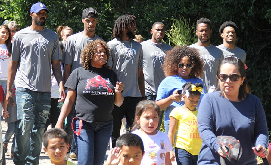 Members of the Wiley College men's basketball team walk in the South Marshall Elementary's